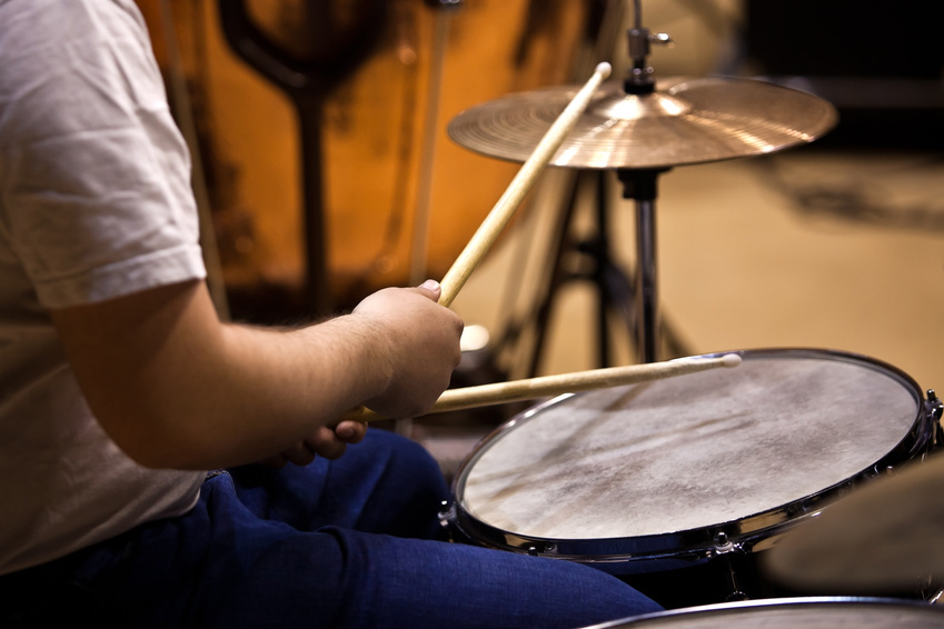Hands of a man playing a drum set